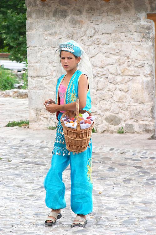 Girl in traditional costume selling fruit to visitors. Pocitelj historic Muslim and Christian village near Mostar. Federation Bosne i Hercegovine. Bosnia Herzegovina, Europe.