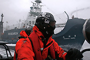 Sea Shepherd crew in a Zodiac inflatable boat race alongside Japanese whaling vessel the Yushin Maru No. 1, in New Zealand territorial waters north of the Ross Sea off Antarctica on Monday, Feb. 2. 2009.  The Yushin used water cannons to keep Sea Shepherd boats at bay.  Sea Shepherd  engaged the ship, along with two other vessels from the Japanese whaling fleet - the Yushin Maru No. 3 and factory vessel, the Nisshin Maru, as part of Operation Musashi, its 2008-2009 campaign to end what it deems to be illegal whaling operations in Antarctic waters. (Photo by Adam Lau)