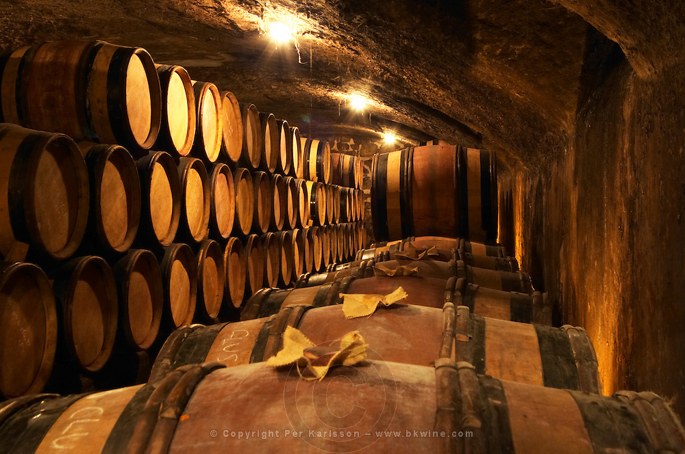 Wooden barrels with aging wine in the cellar of Guigal in Ampuis. In the foreground, barrels with bung hole stoppers of wood and jute.  Domaine E Guigal, Ampuis, Cote Rotie, Rhone, France, Europe