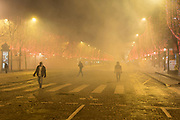 December, 8th, 2018 - Paris, Ile-de-France, France: Demonstrators at end of day's protest, with tear gas smoke, on Champs Elysees. The French 'Gilets Jaunes' demonstrate a fourth day. Their movement was born against French President Macron's high fuel increases. They have been joined en mass by students and trade unionists unhappy with Macron's policies. Nigel Dickinson