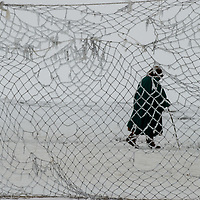 North of the Arctic Circle in Russia, 77-year old Marie Terentéva, a nomadic Komi reindeer herder,  walks in front of a rime-coated net that is carried from camp to camp as a temporary reindeer pen.