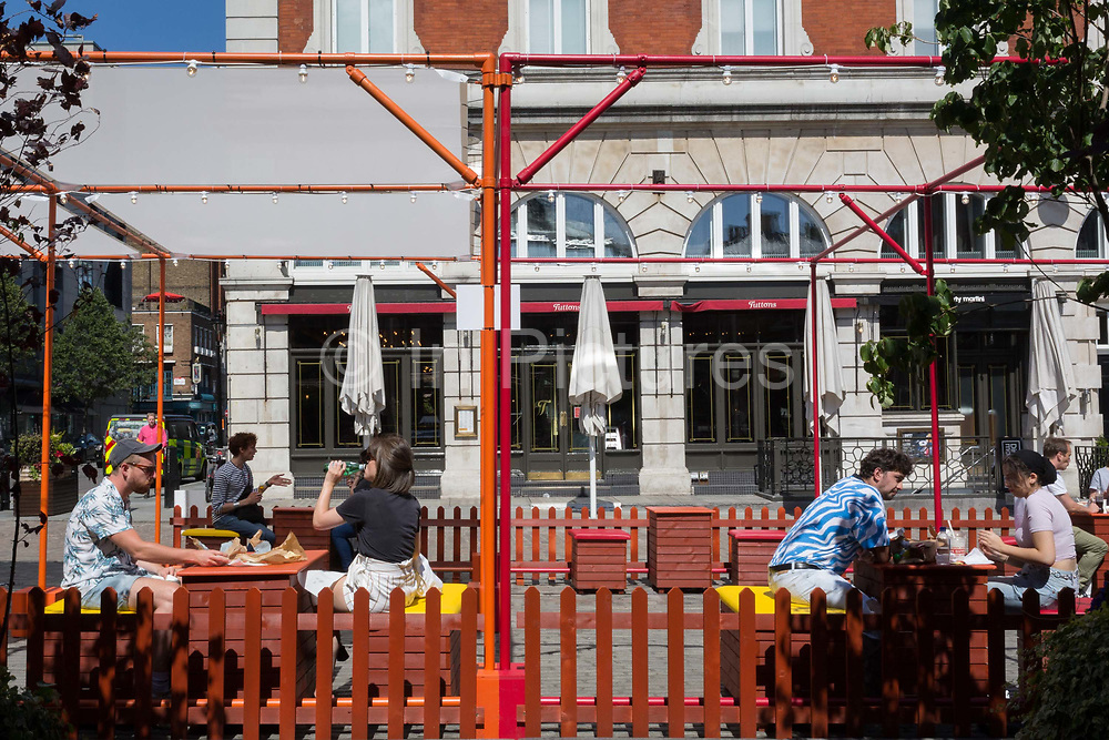 The UK government is considering more easing of the Coronavirus pandemic lockdown rules, a probable change social distance from two metres to 1. However, in the last 24hrs a further 15 have died from Covid, bringing the total to 42,647 and customers sit outside at social distanced tables at a newly-opened cafe in Covent Garden, on 22nd June 2020, in London, England.