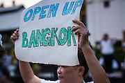 """12 JANUARY 2014 - BANGKOK, THAILAND:  A man carries a sign calling to keep Bangkok open. His sign is a response to anti-government protestors who want to shut Bangkok down. About 500 people from all walks of Thai life came to a candlelight vigil at Thammasat University. They prayed for a peaceful resolution to the political conflict in Thailand. They finished the vigil by singing the John Lennon song """"Imagine."""" Anti-government protestors are expected """"Shutdown Bangkok"""" Monday. There were reports Sunday evening that some intersections were already being blocked.      PHOTO BY JACK KURTZ"""