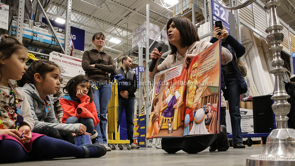 (12/15/19, MILFORD, MA) Rochy Kivman of the Chabad Jewish Center reads a menorah story to children during a menorah building workshop at Lowes in Milford on Sunday. [Daily News and Wicked Local Photo/Dan Holmes]