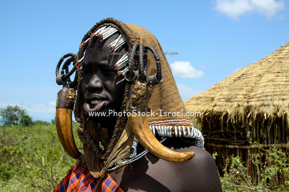 Africa, Ethiopia, Debub Omo Zone, Mursi tribe. A nomadic cattle herder ethnic group located in Southern Ethiopia, close to the Sudanese border. Woman with clay lip disc as body ornaments
