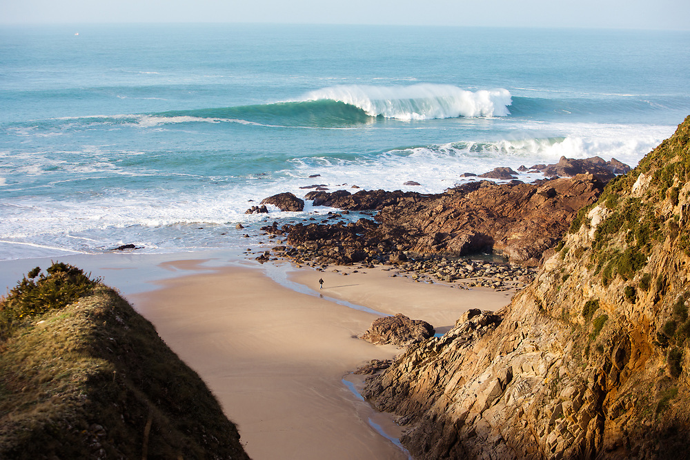 Big waves crashing out at sea at Plemont beach, a beautiful cove on the north west coast of Jersey, Channel Islands