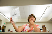 """Yolie Garcia holds up a """"30 Seconds"""" sign to let contestants know they are running out of time in their response during the Milpitas Unified School District Board of Education forum at the Barbara Lee Senior Center in Milpitas, California, on October 2, 2014. (Stan Olszewski/SOSKIphoto)"""