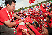 """26 MARCH 2009 -- BANGKOK, THAILAND:  JAKRAPOB PENKAIR, former spokesman for ousted Thai Prime Minister Thaksin Shinawatra signs autographs during an anti-government rally in Bangkok. More than 30,000 members of the United Front of Democracy Against Dictatorship (UDD), also known as the """"Red Shirts""""  and their supporters gathered on Sanam Luang (the vast open field in front of the Palace) and descended on central Bangkok March 26 to start a series of protests against and demand the resignation of current Thai Prime Minister Abhisit Vejjajiva and his government. The protest is a continuation of protests the Red Shirts have been holding across Thailand. Thaksin was deposed in a coup and went into exile rather than go to prison after being convicted on corruption charges. He is still enormously popular in rural Thailand.  PHOTO BY JACK KURTZ"""