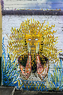 A mural, street art, in Vilcabamba, Ecuador of a man with wild, wild hair and a wild expression on his face.