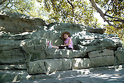 Child (6 years old) sitting in bench carved from rock, near Mrs Macquarie's Chair, The Domain, Sydney, Australia