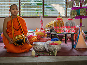 """06 APRIL 2015 - CHIANG MAI, CHIANG MAI, THAILAND: A newly ordained Buddhist novice sits with his alms bowl at the small family alter he had during the three day long Poi Song Long Festival in Chiang Mai. The Poi Sang Long Festival (also called Poy Sang Long) is an ordination ceremony for Tai (also and commonly called Shan, though they prefer Tai) boys in the Shan State of Myanmar (Burma) and in Shan communities in western Thailand. Most Tai boys go into the monastery as novice monks at some point between the ages of seven and fourteen. This year seven boys were ordained at the Poi Sang Long ceremony at Wat Pa Pao in Chiang Mai. Poy Song Long is Tai (Shan) for """"Festival of the Jewel (or Crystal) Sons.   PHOTO BY JACK KURTZ"""