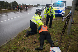 Two Metropolitan Police officers monitor Insulate Britain spokesperson Liam Norton as climate activists arrive to block a slip road from the M25 at Junction 14 close to Heathrow airport as part of a campaign intended to push the UK government to make significant legislative change to start lowering emissions on 27th September 2021 in Colnbrook, United Kingdom. The activists are demanding that the government immediately promises both to fully fund and ensure the insulation of all social housing in Britain by 2025 and to produce within four months a legally binding national plan to fully fund and ensure the full low-energy and low-carbon whole-house retrofit, with no externalised costs, of all homes in Britain by 2030.