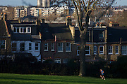 A male jogger runs uphill through his local park in the London Borough of Lambeth.
