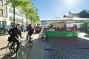 In Groningen passeren fietsers de wekelijkse markt.<br /> <br /> In Groningen cyclists are passing the weekly market.