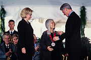Chinese American novelist Maxine Hong Kingston is presented the National Medal of Arts by President Bill Clinton and First Lady Hillary Clinton during a ceremony on the South Lawn of the White House September 29, 1997 in Washington, DC.