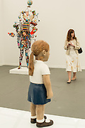 """A wooden statue of a girl by Claudette Schreudes seems to look at a fair attendee. In the background is a colorful piece by Nick Cave, titled """"Soundsuit."""""""