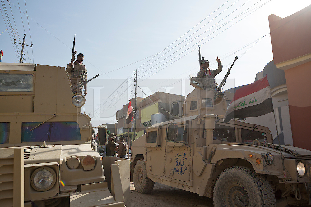 Licensed to London News Pictures. 11/11/2016. Mosul, Iraq. Soldiers, of the Iraqi Army's 9th Armoured Division, stand on armoured Humvees during a visit to Mosul's Al Inisar district on the south east of the city. The Al Intisar district was taken four days ago by Iraqi Security Forces (ISF) and, despite its proximity to ongoing fighting between ISF and ISIS militants, many residents still live in the settlement without regular power and water and with dwindling food supplies.<br /> <br /> The battle to retake Mosul, which fell June 2014, started on the 16th of October 2016 with Iraqi Security Forces eventually reaching the city on the 1st of November. Since then elements of the Iraq Army and Police have succeeded in pushing into the city and retaking several neighbourhoods allowing civilians living there to be evacuated - though many more remain trapped within Mosul.  Photo credit: Matt Cetti-Roberts/LNP