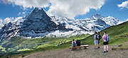 """The Eiger rises above Kleine Scheidegg pass, in the Berner Oberland, Switzerland, the Alps, Europe. The world's longest continuous rack and pinion railway (Wengernalpbahn) goes from Grindelwald up to Kleine Scheidegg and down to Wengen and Lauterbrunnen. From Kleine Scheidegg, Jungfraubahn ascends steeply inside the Eiger to Jungfraujoch, the highest railway station in Europe. UNESCO honors """"Swiss Alps Jungfrau-Aletsch"""" on the list of World Heritage Areas. This image was stitched from multiple overlapping photos."""