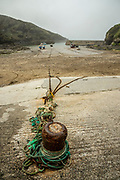 Low tide at Port Isaac on the Cornish Coast of England shows fishing boats tied up with long ropes to an old iron anchoring point just below the village center. Licensing and Open Edition Prints.