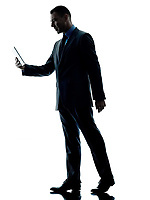 one caucasian business man walking  using digital tablet  silhouette isolated on white background