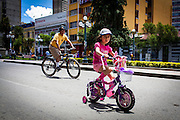 Daughter and father ride bicycles on the 16th July Avenue in central La Paz. During a normal day it would be impossible since this avenue is one of the main arteries of La Paz. During elections period in  Bolivia, the country faces several restrictions, like no alcohol for sale 48 hours before and 12 after the election; no public gatherings, shows of any kind until the political parties made their speeches on the election night; its completely forbidden the circulation of any vehicles, private or governmental except with the permit from the Electoral Tribunal, which means it would be basically no cars, buses or anything circulating in the city; no long distance buses, the terminal will be close from Saturday until Monday and even flights will not be allowed except the ones leaving the country or the international ones doing stop-over. It is a completely shut down of the country.