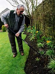 Retired man gardening at home UK