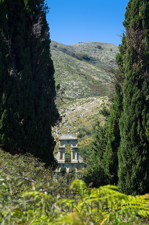 Church of Saint Nikolaos Petra and belfry belltower among cypress trees  in village of Old Perithia - Palea Perithea, Corfu,  Greece