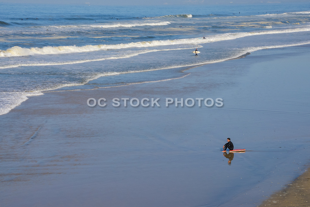 Young Adult Male Sitting on Boogie Board on the Beach Watching Waves