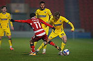 Jack Rudoni of AFC Wimbledon goes past Doncaster midfielder Jon Taylor  during the EFL Sky Bet League 1 match between Doncaster Rovers and AFC Wimbledon at the Keepmoat Stadium, Doncaster, England on 26 January 2021.