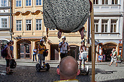 "Tourists on Segways watching and photographing with a smart phone street artists which are performing the ""levitating man illusion"" close to Charles Bridge in the center of Prague."
