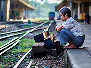 25 NOVEMBER 2017 - YANGON, MYANMAR: A man waits for the Yangon Circular Train. The Yangon Circular Train is a 45.9-kilometre (28.5 mi) 39-station two track loop system connects satellite towns and suburban areas to downtown. The train was built during the British colonial period, the second track was built in 1954. Trains currently run both directions (clockwise and counter-clockwise) around the city. The trains are the least expensive way to get across Yangon and they are very popular with Yangon's working class. About 100,000 people ride the train every day. A a ticket costs 200 Kyat (about .17¢ US) for the entire 28.5 mile loop.    PHOTO BY JACK KURTZ
