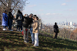 © Licensed to London News Pictures. 27/02/2021. London, UK. Members of the take a selfie in front of the London Skyline in a sunny Greenwich Park in South East London. The national Lockdown is expected to begin to be lifted on the 8th of March with pupils returning to schools and two members of different households allowed to meet outdoors. Photo credit: George Cracknell Wright/LNP