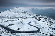A light snow covering defines the wonderfully winding road that passes between Mam Tor & Rushup Edge before entering into Edale. Rushup Edge can be seen to left side whilst Kinder Scout forms the horizon to the right. Winter landscape photography in Derbyshire's Peak District. January.