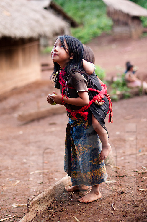 A Hmong girl carries her sister on her back in a small hillside village in Luang Prabang, Laos, Southeast Asia
