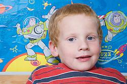 Little boy sitting in his bedroom,
