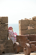A young woman sits at the ramparts of the medina, overlooking the ocean in Essaouira, Morocco