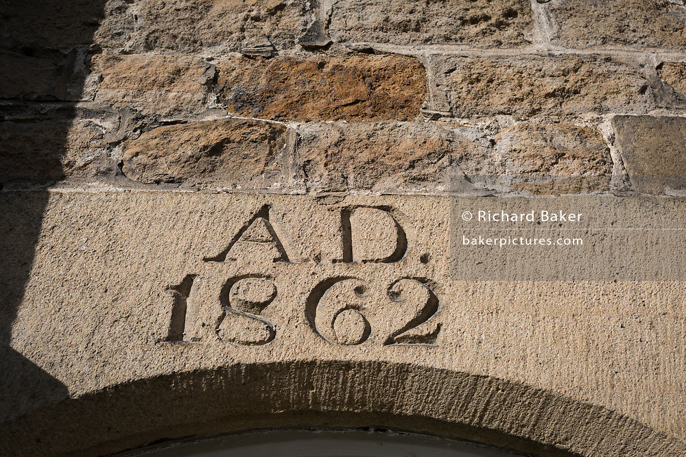 The date of a heritage cottage in the Northumbrian village of Blanchland, on 29th September 2017, in Blanchland, Northumberland, England. Blanchland is a village in Northumberland, England, on the County Durham boundary. The population of the Civil Parish at the 2011 census was 135. Blanchland was formed out of the medieval Blanchland Abbey property by Nathaniel Crew, 3rd Baron Crew, the Bishop of Durham, 1674-1722. It is a conservation village, largely built of stone from the remains of the 12th-century Abbey. It features picturesque houses, set against a backdrop of deep woods and open moors. Set beside the river in a wooded section of the Derwent valley, Blanchland is an attractive small village in the North Pennines Area of Outstanding Natural Beauty.