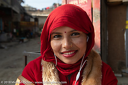 Nepalese women traditionally dresses with her smart phone earbuds in place as she waits for a bus. Kathmandu after our Himalayan Heroes motorcycling adventure, Nepal. Saturday, November 17, 2018. Photography ©2018 Michael Lichter.