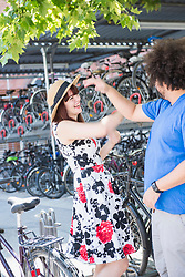 Happy young couple dancing in city by bicycle parking