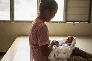 20 MAY 2013 - MAE KASA, TAK, THAILAND: A Burmese woman holds her newborn grandchild in the delivery area of the SMRU clinic in Mae Kasa, Thailand.  Health professionals are seeing increasing evidence of malaria resistant to artemisinin coming out of the jungles of Southeast Asia. Artemisinin has been the first choice for battling malaria in Southeast Asia for 20 years. In recent years though,  health care workers in Cambodia and Myanmar (Burma) are seeing signs that the malaria parasite is becoming resistant to artemisinin. Scientists who study malaria are concerned that history could repeat itself because chloroquine, an effective malaria treatment until the 1990s, first lost its effectiveness in Cambodia and Burma before spreading to Africa, which led to a spike in deaths there. Doctors at the Shaklo Malaria Research Unit (SMRU), which studies malaria along the Thai Burma border, are worried that artemisinin resistance is growing at a rapid pace. Dr. Aung Pyae Phyo, a Burmese physician at a SMRU clinic just a few meters from the Burmese border, said that in 2009, 90 percent of patients were cured with artemisinin, but in 2010, it dropped to about 70 percent and is now between 55 and 60 percent. He said the concern is that as it becomes more difficult to clear the parasite from a patient, progress that has been made in combating malaria will be lost and the disease could make a comeback in Southeast Asia.    PHOTO BY JACK KURTZ