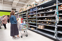 © Licensed to London News Pictures. 21/09/2020. London, UK. A customer buys pasta from virtually empty shelves at an Asda supermarket in Wembley. Some shoppers have been reported to start panic buying items including toilet paper and household good ahead of a feared second wave of Covid-19. Photo credit: London News Pictures