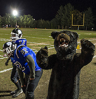 """Winnisquam's """"Bear"""" mascot gets the crowd fired up for their Homecoming game against Franklin  under the lights Friday night.  (Karen Bobotas/for the Laconia Daily Sun)"""