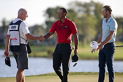 February 25, 2018 - Palm Beach Gardens, Florida, U.S. - Tiger Woods shakes hands with his caddie, Joe LaCava, as Sam Burns looks on after completing the 18th hole during the final round of the 2018 Honda Classic at PGA National Resort and Spa in Palm Beach Gardens, Fla., on Sunday, February 25, 2018. (Credit Image: © Andres Leiva/The Palm Beach Post via ZUMA Wire)