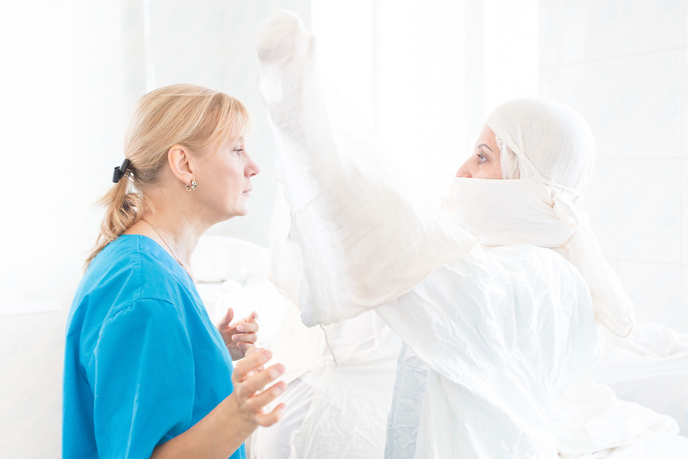 CAPTION: Surgical nurse Irina Shukova helps Maxillofacial surgeon Dr Fomenko with the headscarf that will keep all her germs contained while she undertakes surgery. LOCATION: Volgograd City Hospital #1, Volgograd, Russia. INDIVIDUAL(S) PHOTOGRAPHED: Dr Irena Fomenko (left) and Irina Shukova (right).