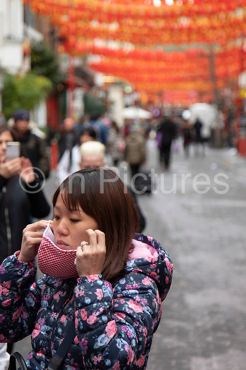 People wearing face masks on Gerrard Street in Chinatown on 27th January 2020 in London, England, United Kingdom. Due to the recent coronavirus outbreak an increased number of Chinese and Asian people are wearing face masks in public despite NHS Englands advice that the risk of getting the illness in the UK is low. Wuhan novel coronavirus WN-CoV is a new respiratory illness that has not previously been seen in humans. Each year local Chinese community and Londoners gather on this famous area of central London which is the focus of celebrations for this, the Chinese Year of the Rat. Bright red lanterns are strung across between the buildings creating a canopy of colour.