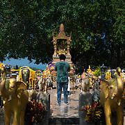 Young man praying in the shrine to elephants on Promthep cape, Phuket, Thailand