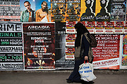 Street scene in Whitechapel in East London, England, United Kingdom. A woman passes posters for various club nights.