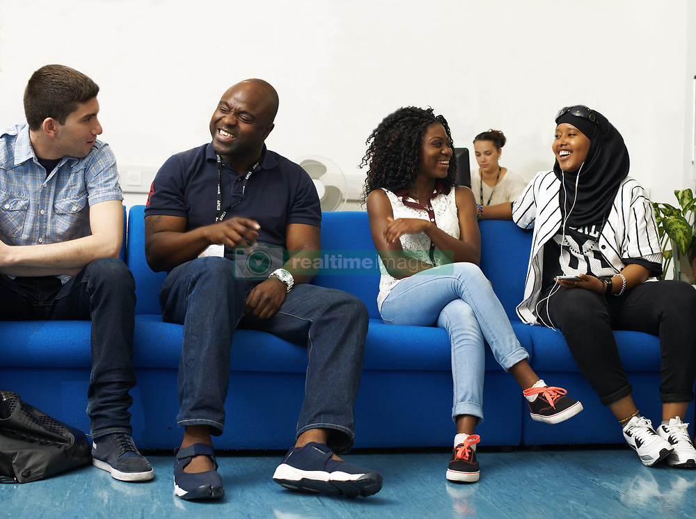 June 25, 2014 - Male lecturer chatting to students in college (Credit Image: © Image Source/Image Source/ZUMAPRESS.com)