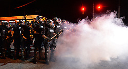 Charlotte-Mecklenburg police officers in riot gear stand in a haze of tear gas watching protestors on Old Concord Rd. on Tuesday night, Sept. 20, 2016 in Charlotte, N.C. The protest began on Old Concord Road at Bonnie Lane, where a Charlotte-Mecklenburg police officer fatally shot a man in the parking lot of The Village at College Downs apartment complex Tuesday afternoon. The man who died was identified late Tuesday as Keith Scott, 43, and the officer who fired the fatal shot was CMPD Officer Brentley Vinson. Photo by Jeff Siner/Charlotte Observer/TNS/ABACAPRESS.COM