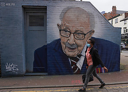 © Licensed to London News Pictures. 1/04/2021. Manchester, UK. A member of the public wearing a face mask walks past a mural painted by grafitti artist Akse_P19 depicting Captain Sir Thomas Moore in Central Manchester. Photo credit:  Ioannis Alexopoulos/LNP